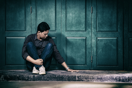 handsome lonely man in frustrated depression sitting alone on the floor., looking and touch at empty space nobody beside him., Concept of lonely, sadness, alone, depressed and human problems.