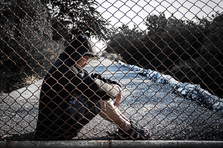 Depressed man wearing a black hoodie sitting on the ground are sadness and frustrated in his life., behind a fence steel mesh cage, no freedom.