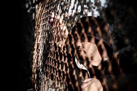 Depressed man wearing a black hoodie sitting on the ground are sadness and frustrated in his life., behind a fence steel mesh cage.,looking to outside no freedom.