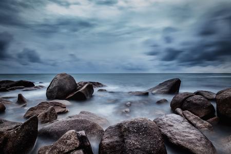 Donkere rotsen in een blauwe oceaan onder bewolkte hemel in een slecht weer., Lange belichtingsfotografie. Stockfoto - 73042855