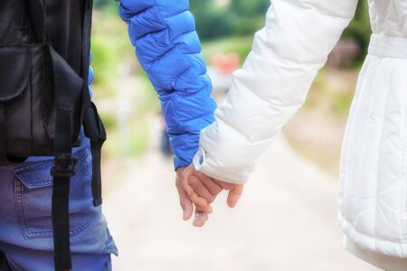 Close-up of a happy couple in love holding hands and walking together in the garden., romance and love concept for valentines day.