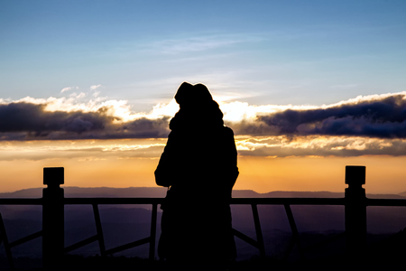 silhouette of a beautiful woman standing on panoramic viewpoint., looking to the horizon and enjoying a beautiful sunset behind the mountain. Banco de Imagens - 72758064