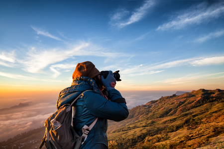 Beautiful women professional photographer takes images with DSLR camera., on the mountain with morning sunlight and fog.