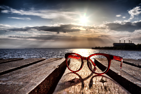 Beautiful spectacles on wooden bridge extended into the sea near the beach., with factory and sunset behind. Stockfoto