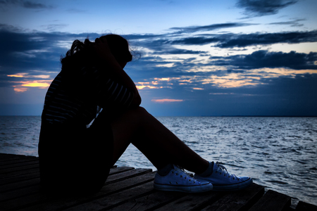 Beautiful woman in frustrated depression sitting on wooden bridge, near the beach on sunset. Concept of unemployed, sadness, depressed and human problems in dark tone. Banco de Imagens
