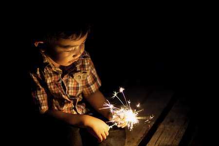 Cute little boy with a funny face holding sparklers., Image with selective focus and toning.