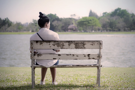 Beautiful lonely woman in frustrated depression sitting alone on bench in park., Concept of lonely, sadness, alone, depressed and human problems.