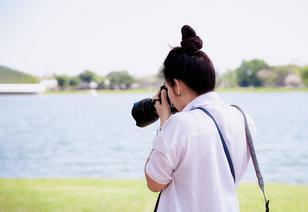 Beautiful women professional photographer takes images with DSLR camera., In the park. Banco de Imagens
