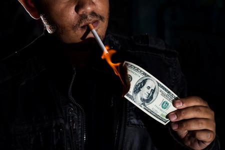 Gangster maffia killer of drugsdealer met behulp van de dollar biljet zwart geld ontvangen van de illegale handel of het verkopen van drugs en verdovende middelen aansteken van zijn sigaret tabak., In donkere toon. Stockfoto - 72758058