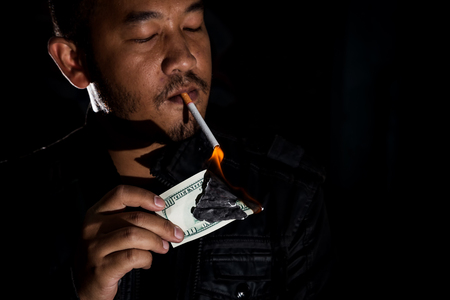Gangster mafia killer or drug dealer using dollar banknote dirty money received from the illegal business or selling drugs and narcotics lighting his cigarette tobacco., In dark tone.