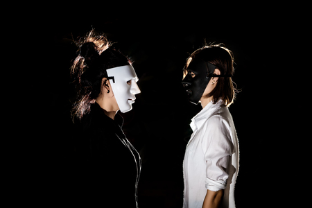Conflict confrontation between beautiful woman in black mask and white mask in scary abandoned building., Good and Bad of mind to choose temptation concept.