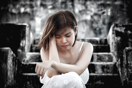 woman in frustrated depressed sitting on stairs, crying and contemplating suicide, in scary abandoned building, Concept of unemployed, sadness, depression, broken heart and human problem in dark tone. Stockfoto