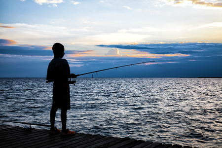 Silhouette of the boy fishing on wooden bridge extended into the sea on sunset. Stockfoto