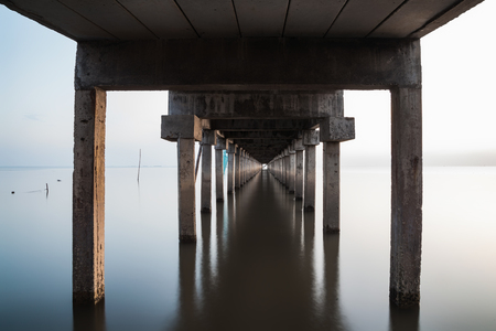 under view of bridge extended into the sea with water reflection., long exposure photography., the concept of lonely, sadness, depressed and broken heart.