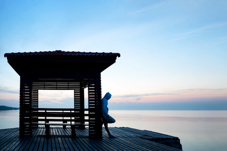 Frustrated depressed man wearing hoodie standing alone on wooden bridge extended into the sea looking down and contemplating suicide., Concept of unemployed, sadness, depression and human problems.