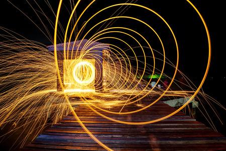 Hot Golden Sparks vliegend vanaf Man Spinning Brandende Staal wol op houten brug Extended in de zee., Lange Fotografie Exposure behulp Staalwol Burning. Stockfoto - 73065102