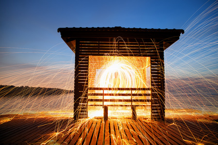 Hot Golden Sparks Flying from Man Spinning Burning Steel Wool on Wooden Bridge Extended into the Sea., Long Exposure Photography using Steel Wool Burning.