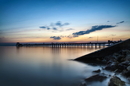 Dark rock dam in blue ocean on twilight sunset and wooden bridge extended into the sea with water reflection., long exposure photography., the concept of lonely, sadness, depressed and broken heart. Stockfoto