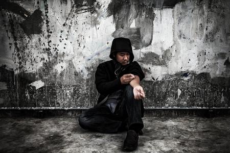 Drug abuse concept., Overdose asian male drug addict in action with drugs narcotic syringe in hand. Banco de Imagens