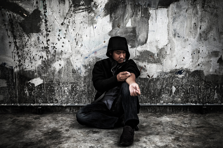 Drug abuse concept., Overdose asian male drug addict in action with drugs narcotic syringe in hand. Stockfoto