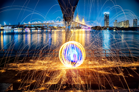 Hot Golden Sparks Flying from Man Spinning Burning Steel Wool under Bhumibol Bridge in Bangkok Thailand., Long Exposure Photography using Steel Wool Burning.