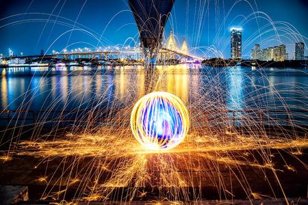 Hot Golden Sparks Flying from Man Spinning Burning Steel Wool under Bhumibol Bridge in Bangkok Thailand., Long Exposure Photography using Steel Wool Burning.