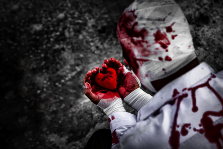 seriously injured man in body wraps bandages bleeding in frustrated depression from unrequited love. holding the red heart smeared with blood in hand. love concept for valentines day. in dark tone.