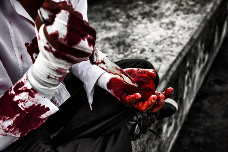 seriously injured man body wraps bandages bleeding in depression from unrequited love. use a knife smeared with blood stabbing a red heart in hand. love concept for valentines day. in dark tone. Stock Photo