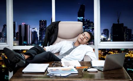 Het gevoel uitgeput., Jonge Aziatische zakenmanzitting op laag in bureau., Slapend terwijl het werken met computer op zijn werkende plaats., Op het bureau dat door administratie wordt overweldigd. Stockfoto - 95720351