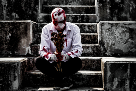 seriously injured man body wraps bandages bleeding in depression from unrequited love sitting on the stairs, holding the bouquet of dried roses, love concept for valentines day. in dark tone.