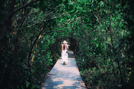 Beautiful traveller woman in white dress, sneaker and straw hat with dslr camera walking on the old wooden bridge extended into the dark forest.
