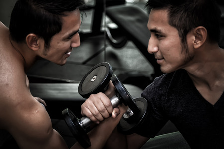 Two Asian men use dumbbell exercise weight-lifting arm-wrestle compete in fitness gym