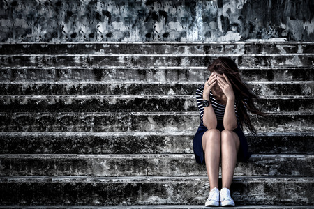 Beautiful woman in frustrated depression sitting on the stairs, in scary abandoned building. Concept of unemployed, sadness, depressed and human problems in dark tone.