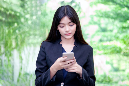 Happy Asian female watching her photos on cell telephone while relaxing in garden at workplace, charming business woman with beautiful smile reading good news on mobile phone during rest in park.