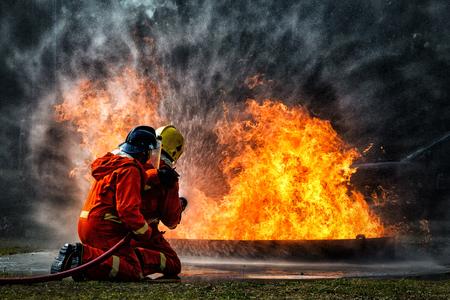entrenamiento de bomberos., bombero usando agua y extintor para combatir con llama de fuego en una situación de emergencia., bajo situación de peligro, todos los bomberos usan traje de bombero por seguridad.