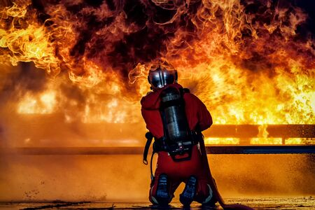 Firefighter training., fireman using water and extinguisher to fighting with fire flame in an emergency situation., under danger situation firemen wearing fire fighter suit for safety.