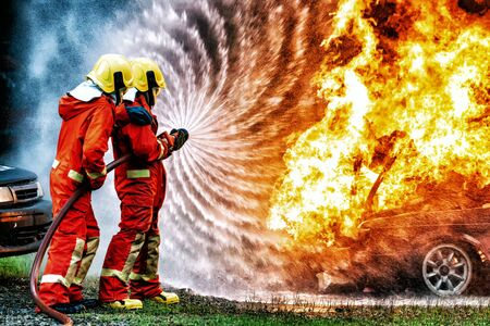formación de bomberos., bombero que usa agua y extintor para luchar con llama de fuego en un coche accidentado en la carretera., en situación de peligro, todos los bomberos usan traje de bombero por seguridad. Foto de archivo