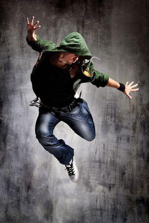 tanieć: coll tancerz stanowiących patrząc na szary mur grunge