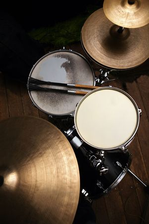 drumming: drum set in dramatic light on a black background