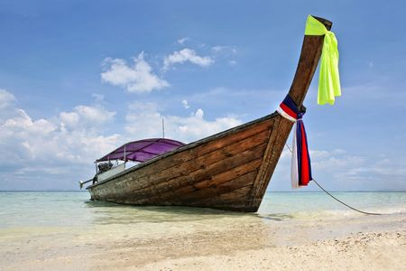 beautiful longtail boat on the sand seashore photo