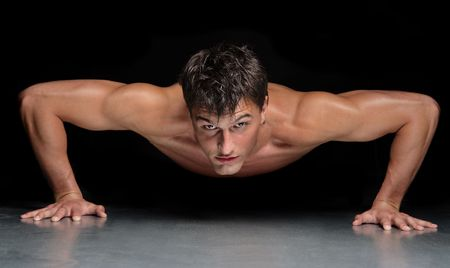 young male doing physical exersize on a dark background photo