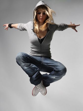hiphop: young female jumping on the grey background