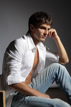 young male in white shirt on grey baclground photo