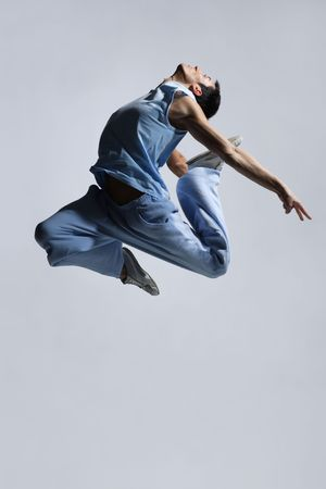 stylish modern  dancer jumping on grey