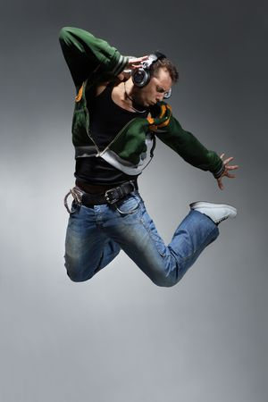 listening music: cool looking dancer makes a difficult jump