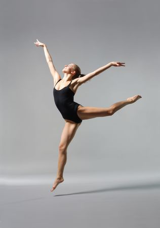 young and beautiful ballet dancer posing on gery photo