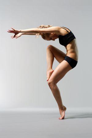 danza moderna: hermosa joven bailarina posando sobre fondo gris