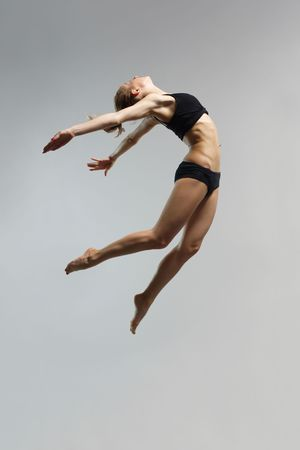 acrobacia: joven y hermosa mujer saltando de alta Foto de archivo