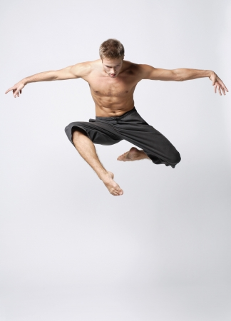 leap: modern ballet dancer posing over white background