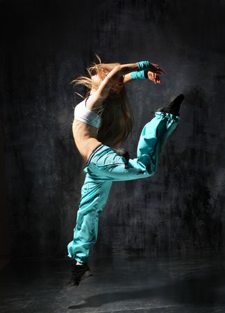 leap: modern style dancer posing behind studio background Stock Photo